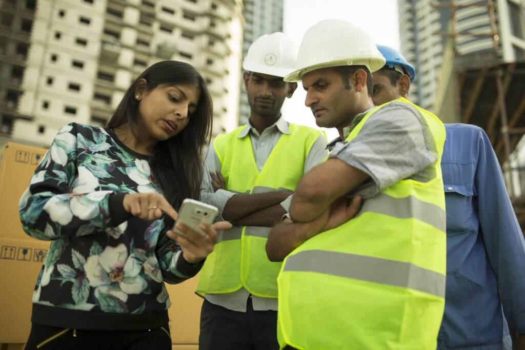 Construction workers using NOW Money app with NOW Money team.